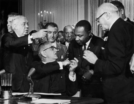 Lyndon B Johnson shakes Martin Luther King's hand at the signing of the civil rights act.