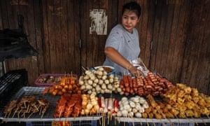 A woman arranges fried snacks on her street food cart the Pratunam district of Bangkok.