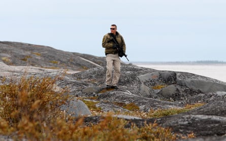 A member of the RCMP watches for polar bears at the Cape Merry National Historic Site in ChurchillA member of the Royal Canadian Mounted Police watches for polar bears at the Cape Merry National Historic Site in Churchill, Manitoba August 23, 2010 during a visit by Canada's Prime Minister Stephen Harper.