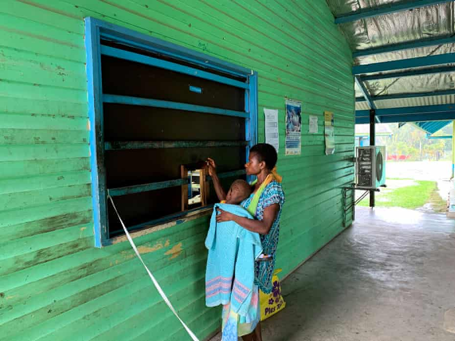 A woman holds her child as they wait for medicine at the dispensary at Warangoi Helth Clinic.