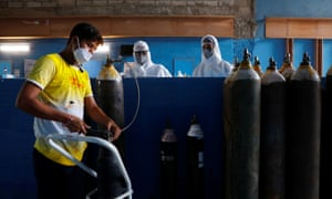 A worker refills an oxygen cylinder at a hospital in Noida on the outskirts of New Delhi, India, on Tuesday.