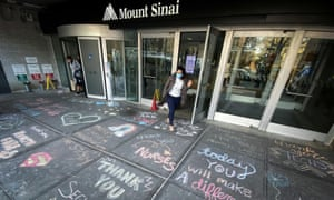 A woman exits Mount Sinai hospital, where messages of thanks to healthcare workers are written on the sidewalk, in New York City Tuesday.