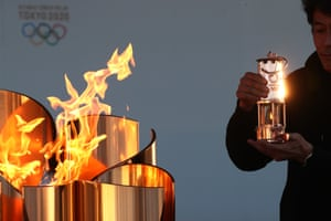 Iwaki, Japan: a member of staff preserves the Olympic flame in a lantern