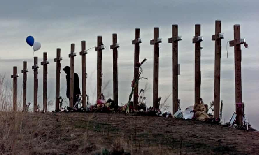An unidentified woman looks at 15 crosses posted on a hill above Columbine high school in Littleton, Colorado.