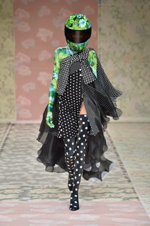 A model on the catwalk in black tights with white polka dots and flowing scarves in black and white. Her arms are green floral with a matching helmet which covers her face