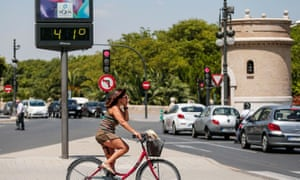 A cyclist waits to cross a road next to a thermometer showing 41C in Valencia, eastern Spain.