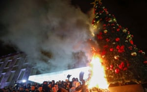 Demonstrators set fire to a Christmas tree during a protest in reaction to the killing of Klodian Rasha.