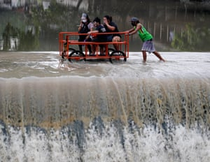 manoeLas Pinas, Philippines, Villagers riding a rickshaw manoeuvre along an overflowing dam uvre