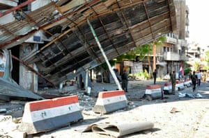 Syrian army soldiers stand at the site of an explosion in Bab Tadmor, Homs.