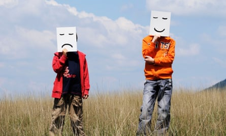 Boys in Field holding Drawn Facial Expressions
