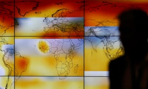 A participant  in front of a screen projecting a world map with climate anomalies during the World Climate Change Conference 2015 (COP21) at Le Bourget