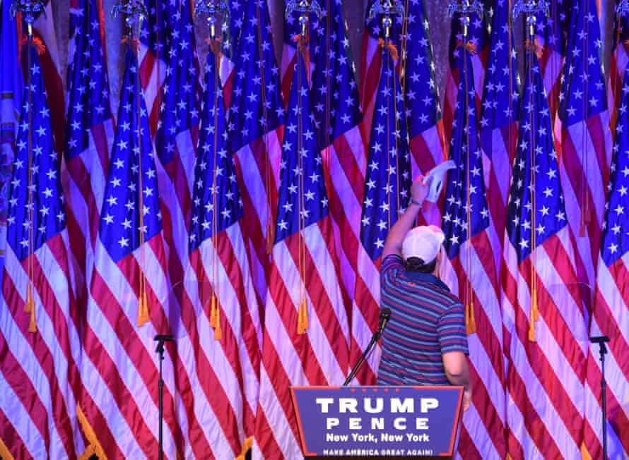 A man vacuums US flags on the stage where Donald Trump will speak later.