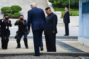 US President Donald Trump steps into the northern side of the Military Demarcation Line that divides North and South Korea, as North Korea's leader Kim Jong Un looks on.