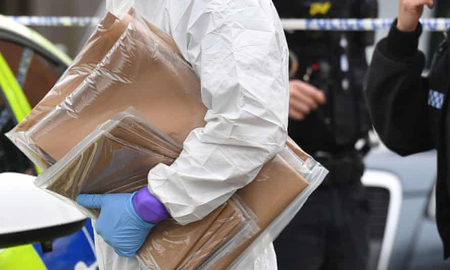 A close-up of a person wearing a white boiler suit and blue gloves carrying plastic wrapped packages against a backdrop of police tape