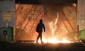 Rioter near burning iron doors in Belfast