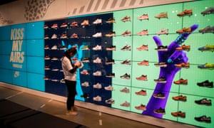 A staff member puts trainers on a shelf at a Nike shop