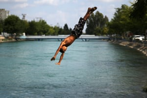 Adana, Turkey A boy jumps into a channel used for agricultural irrigation