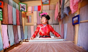 A Mosuo woman weaves with a loom at her shop in Lijiang, China.