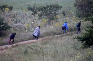 Idomeni, Greece: A group of men run to avoid being transferred to government camps