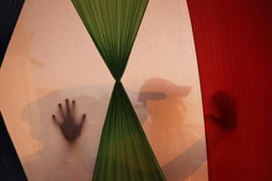 A child is silhouetted behind a flag in a tent on Gaza beach