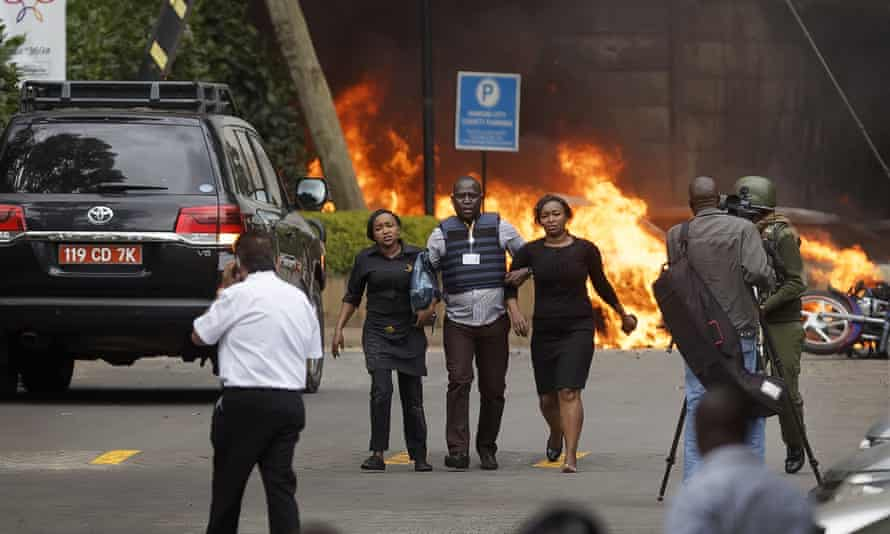 Security forces help civilians flee the scene as cars burn at a hotel complex in Nairobi, Kenya, in January.