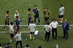 Japan team players and coaches wait for confirmation of the result of the Senegal v Columbia game.