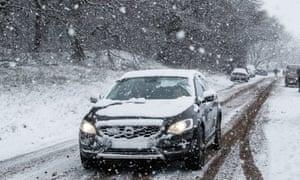 A car drives through snow