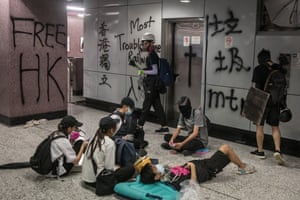 Protesters rest inside the vandalized Causeway Bay MTR station after clashing with police at an anti-government rally on August 31, 2019