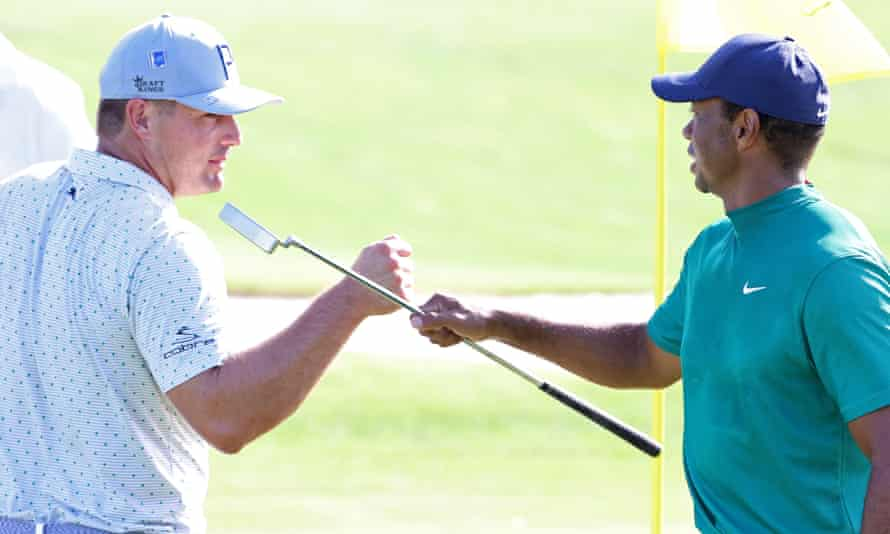 Tiger Woods and Bryson DeChambeau bump fists during a practice round at Augusta
