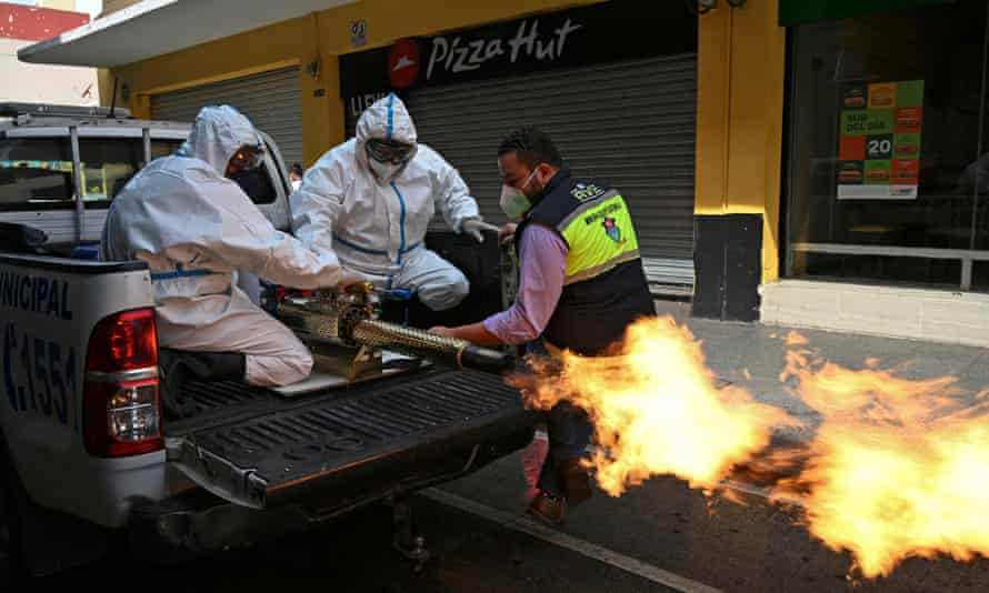 Municipal workers wearing protective gear disinfect the streets in Guatemala City. The pandemic is at its worst moment yet, and discontent is growing.
