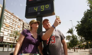 Tourists take a selfie with a thermometer reading 49C in Córdoba