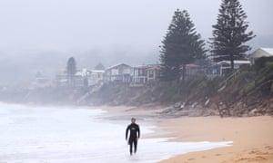 A surfer walks past damaged houses along Wamberal beach