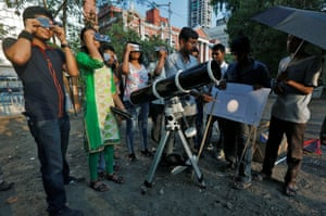 People wear solar filters at a public viewing in Kolkata, India