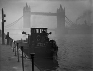 A tugboat on the Thames near Tower Bridge in heavy smog, December 1952