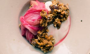 A slice of rhubarb curled over next to clusters of granola resting on yogurt