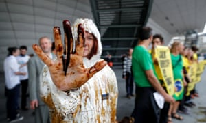 A Greenpeace activist shows her oil-covered hand at the protest outside Total's annual shareholders' meeting.