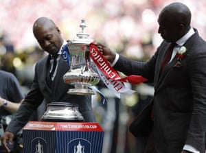 Eddie Newton, left, and Sol Campbell stick the cup onto the plinth.