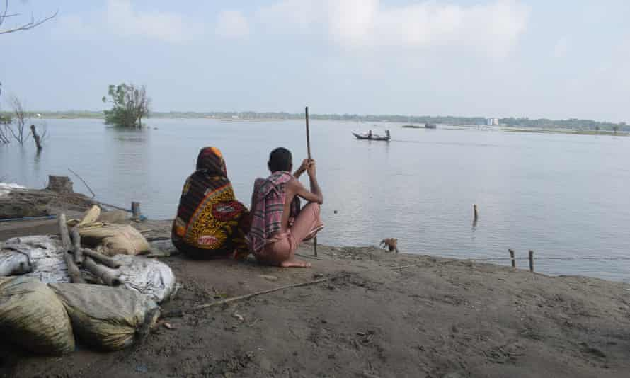 Abdus Sattar Ghazi and his wife Zahera Khatun watch the water levels by their house.