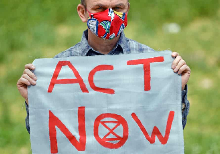 Man in a face mask holds banner saying Act Now