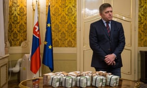 Robert Fico stands behind bundles of euros in Bratislava.