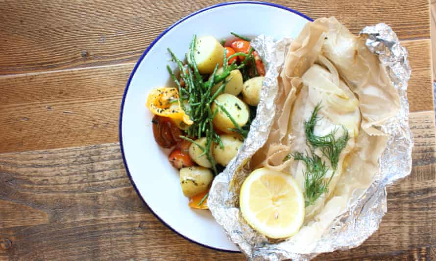 Seafood dish, served in foil, on a plate with boiled potatoes and roasted vegetables at Havener's Bar & Grill, Fowey, Cornwall, UK.