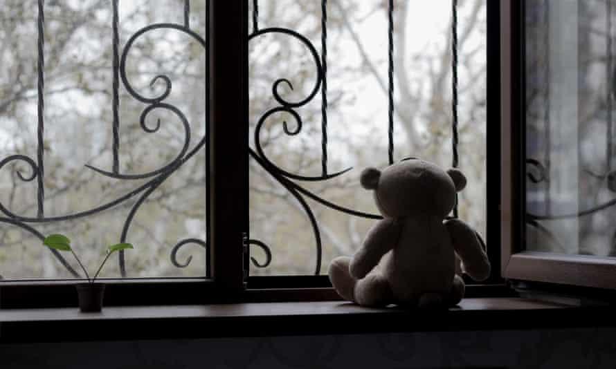 teddy bear looks out window