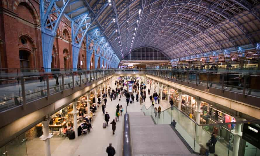 Picture of London St Pancras with people walking along the sunken concourse and its famous arched roof illuminated in purple and blue