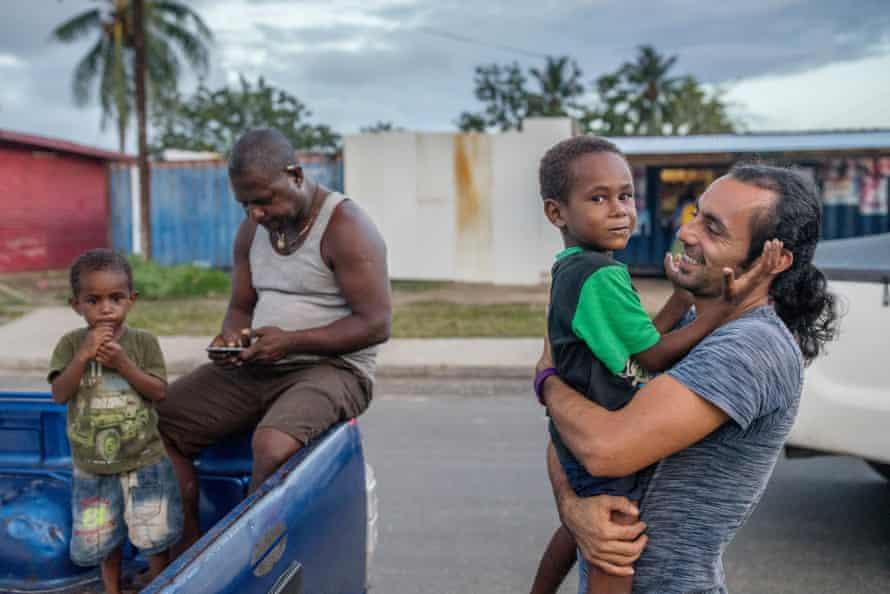 An Iranian refuge hugs a local child on Manus Island.