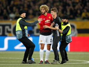 Stewards apprehend the smiling pitch invader as he approaches Manchester United's Marouane Fellaini.