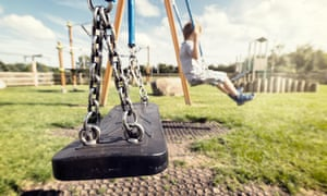 Empty playground swing with children playing in the background