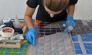 An artist works on restoring the tiles.