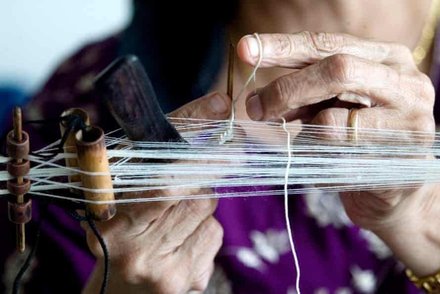 A Parsi woman ties a kusti, the sacred thread worn by Zoroastrians.