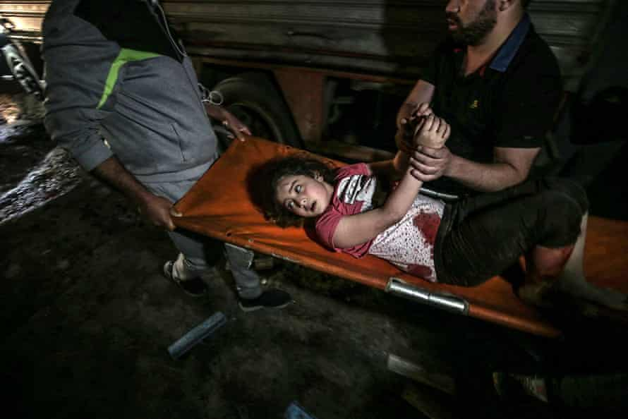 Palestinian Civil Defence men carry a wounded girl after an Israeli air strike in Gaza City, 16 May.
