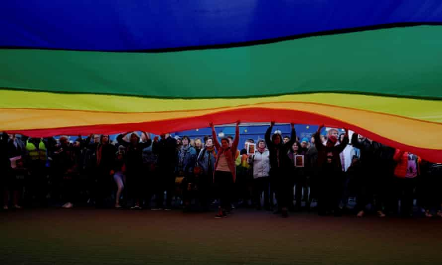 People hold a large rainbow flag during a protest in support of Elzbieta Podlesna who was detained for offending religious beliefs.